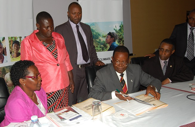 The Minister signing the Strategy. On the left: Rachel Musoke, representing the Permanent Secretary, MWE, and Members of the Parliamentarian Forum on Climate Change. On the right: H.E. Abel Rwendeire, Deputy Chair of the NPA, and Safiou Esso Ouro-Doni, UNDP Deputy Country Director.
